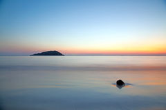 falta de definición de movimiento del mar debajo del cielo crepuscular vivo de la puesta del sol Foto de archivo libre de regalías