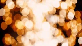 Falta de definición del bokeh del círculo del movimiento de las luces amarillas de los fuegos artificiales de la lluvia durante p almacen de video