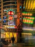 Falta de definición de movimiento del autobús y de la silueta móviles bajo luces de neón en la noche, Hong Kong imagenes de archivo