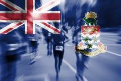 Falta de definición de movimiento del corredor de maratón con la bandera de mezcla de las Islas Caimán Foto de archivo libre de regalías