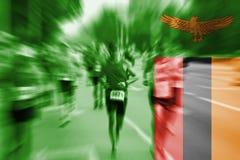 Falta de definición de movimiento del corredor de maratón con la bandera de mezcla de Zambia Imagen de archivo