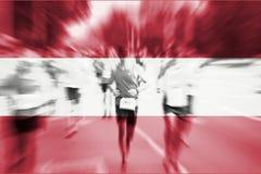 Falta de definición de movimiento del corredor de maratón con la mezcla de la bandera de Austria Foto de archivo