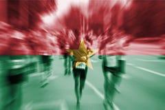 Falta de definición de movimiento del corredor de maratón con la mezcla de la bandera de Burkina Faso Imágenes de archivo libres de regalías
