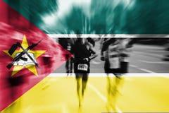 Falta de definición de movimiento del corredor de maratón con la mezcla de la bandera de Mozambique Imágenes de archivo libres de regalías