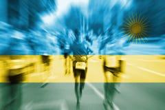 Falta de definición de movimiento del corredor de maratón con la mezcla de la bandera de Rwanda Fotos de archivo libres de regalías