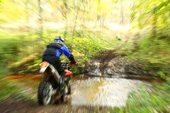 Falta de definición de movimiento, río campo a través de la travesía de la moto Imagenes de archivo