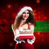 Falta de sorriso atrativa Santa com um presente Fotos de Stock Royalty Free