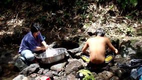 Falta de utilidades de circuito de agua públicas en las comunidades rurales filipinas, fuerzas esta mujer para lavar la ropa incl metrajes