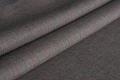 Falten des grauen woolen Stoffes Stockfotos