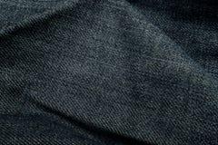 Falten Sie dunkelblauen Jeansbeschaffenheitshintergrund Stockbild