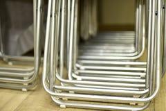 Faltende Metallstühle gemacht von den Rohren in Folge gestapelt stockbild
