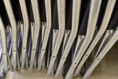 Faltende Metallstühle gemacht von den Rohren in Folge gestapelt stockfoto