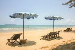 Faltende Strand-Stühle mit Regenschirmen Stockbild
