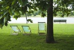 Faltestühle und Parkbank Stockfotos