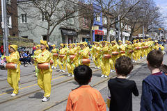 Falun Dafa marching group dressed in traditional Chinese costume play waist drum during the Beaches Easter Parade 2017 on Queen St. Reet East Toronto Royalty Free Stock Images