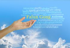 Falun Gong a Chinese system of spiritual teachings Word Cloud. Female hand with open palm reaching up to the words FALUN GONG surrounded by a relevant word cloud stock image