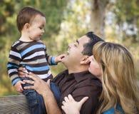 Família étnica feliz da raça misturada que joga no parque fotos de stock royalty free