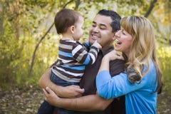 Família étnica feliz da raça misturada que joga no parque imagem de stock royalty free