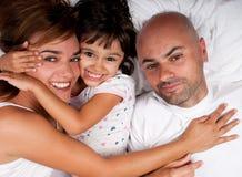 Família abraçada na cama Imagem de Stock Royalty Free