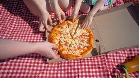 A família abre uma caixa da pizza do cartão, a seguir as mãos tomam a parte de dar água na boca video estoque