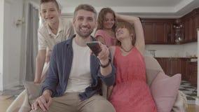 Família adorável feliz do retrato que olha a tevê em casa junto O pai guarda o telecontrole e comuta os canais, vídeos de arquivo