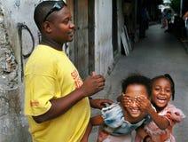 A família africana, homem negro e duas meninas de pele escura, caçoa o jogo. Imagem de Stock