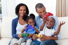 Família afro-americana feliz que joga os jogos video