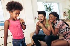 A família afro-americano aprecia cantar o karaoke imagem de stock
