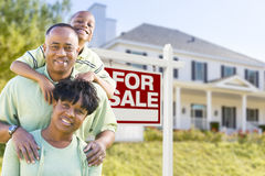 Família afro-americano na frente do sinal e da casa da venda Foto de Stock Royalty Free