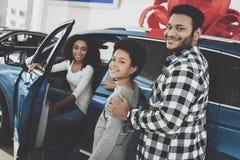 Família afro-americano no concessionário automóvel Pai, mãe e filho estando perto do carro novo imagem de stock royalty free