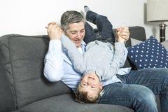 A família agradável senta-se no sofá da sala de visitas Fotos de Stock