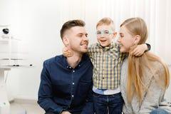 Família alegre com o oftalmologista pequeno do doutor da recepção da criança que usa vidros imagens de stock royalty free