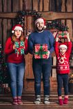 Família alegre com os presentes em suas mãos para o Natal imagem de stock