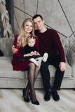 Família alegre e jovial com o bebê no sofá cinzento imagem de stock