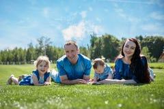 A família alegre em um parque, os pais e suas duas crianças estão encontrando-se na grama Tiro com alargamento foto de stock royalty free
