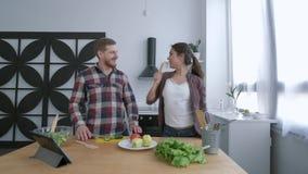 Família alegre, esposa atrativa com dança do marido e divertimento ter ao cozinhar a refeição saudável dos vegetais sobre video estoque