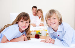 Família alegre que come o pequeno almoço sentar-se na cama imagens de stock