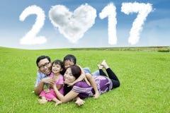 Família alegre que encontra-se na grama com 2017 Imagem de Stock