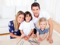 Família alegre que joga o mikado na sala de visitas imagem de stock