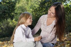 Família alegre que senta-se nas folhas de outono Imagem de Stock
