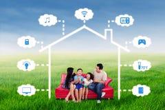 Família alegre que senta-se sob o projeto esperto da casa imagens de stock