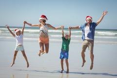 Família alegre que veste o chapéu de Santa ao saltar na praia Foto de Stock