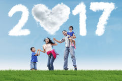 A família alegre salta no campo com 2017 Fotos de Stock