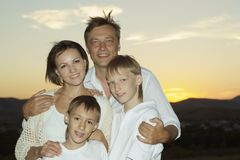 Família amigável contra o por do sol Fotografia de Stock Royalty Free