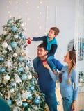A família amigável feliz que decora a árvore de Natal tem o divertimento imagem de stock