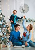 A família amigável feliz que decora a árvore de Natal tem o divertimento imagens de stock