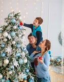 A família amigável feliz que decora a árvore de Natal tem o divertimento fotografia de stock royalty free