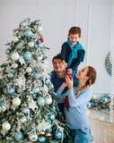 A família amigável feliz que decora a árvore de Natal tem o divertimento fotografia de stock