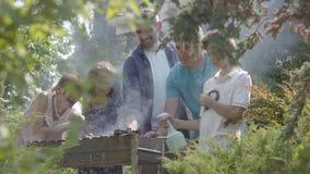 Família amigável feliz que faz o BBQ no close-up do jardim Lazer do ver?o Povos que cozinham a carne na grade fora filme