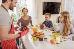 Família amigável que come o café da manhã na cozinha imagem de stock